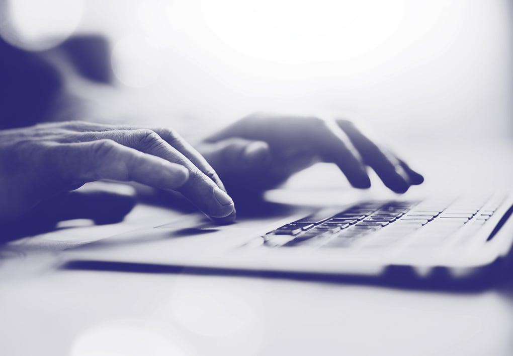 Une personne qui écrit sur un ordinateur.